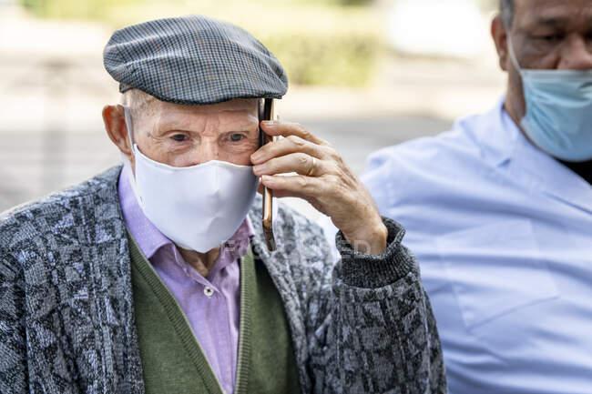 Старший чоловік, який розмовляє на смартфоні в захисній масці, сидить з дорослим чоловіком під час COVID-19. — стокове фото