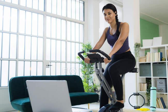 Молодая женщина слушает музыку через Bluetooth, сидя на велосипеде дома — стоковое фото