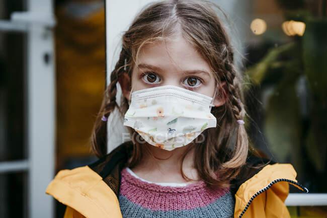 Chica usando mascarilla mientras está de pie contra la puerta - foto de stock
