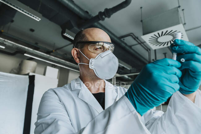 Científico usando mascarilla protectora y anteojos que sostienen la vacuna mientras está de pie en el laboratorio - foto de stock