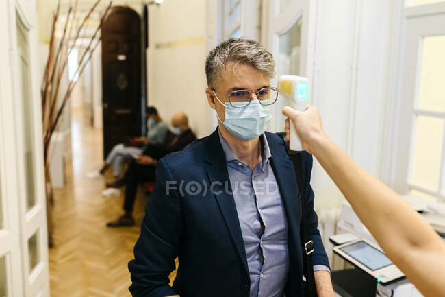 Рука самки з інфрачервоним термометром перевіряє температуру дорослого бізнесмена в коридорі. — стокове фото