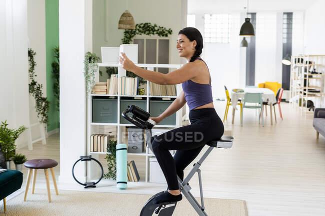 Молода жінка, сидячи вдома на велосипеді. — стокове фото