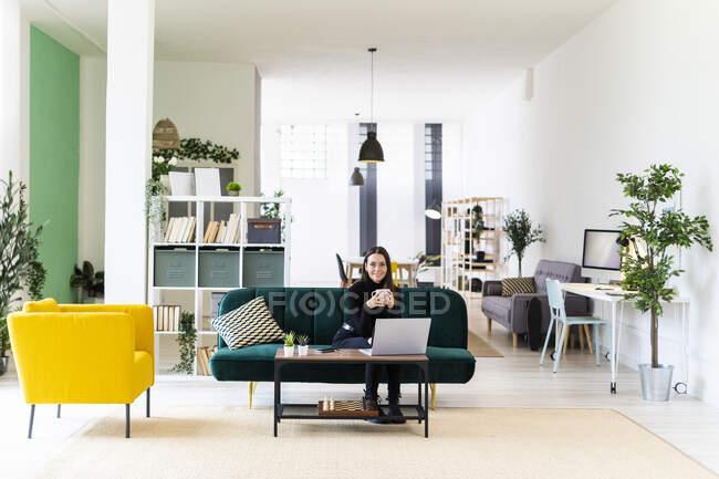 Улыбающаяся красивая женщина-влиятель сидит дома с чашкой кофе и ноутбуком — стоковое фото