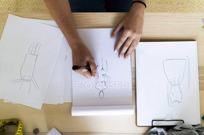 Female designer's hand drawing sketch in book at studio — Stock Photo