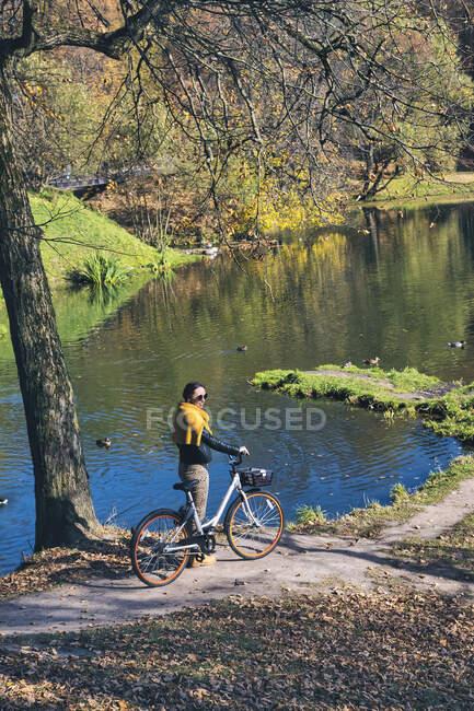 Frau mit Fahrrad steht an sonnigem Tag im öffentlichen Park — Stockfoto
