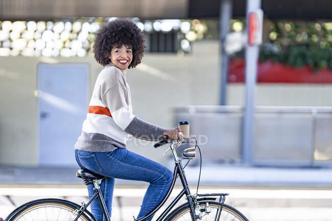 Femme heureuse regardant loin tout en étant assis sur le vélo à la gare — Photo de stock