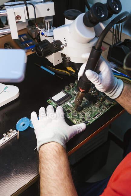 Reparador usando tocha de sopro na placa de circuito na bancada na oficina — Fotografia de Stock