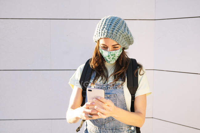 Mature woman using smart phone wearing protective face mask standing against wall on sunny day — Stock Photo