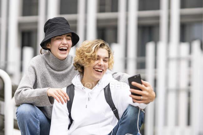Jóvenes amigos riendo mientras toman selfie en el teléfono móvil - foto de stock