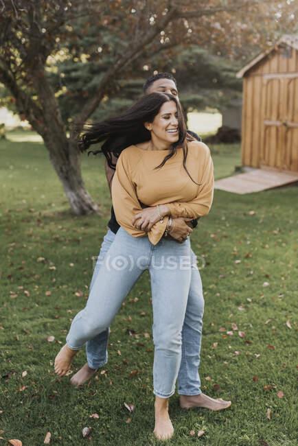 Чоловік обертається жінка, стоячи на задньому дворі. — стокове фото