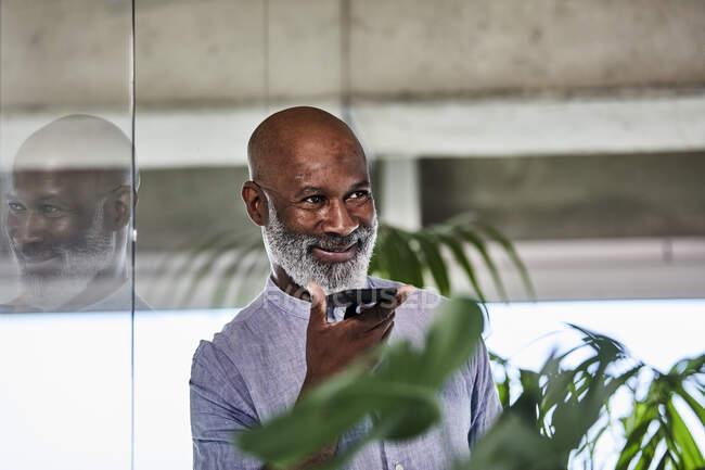 Посмішка дорослого бізнесмена, який слухає дзвінок через смартфон, спираючись на скляну стіну. — стокове фото