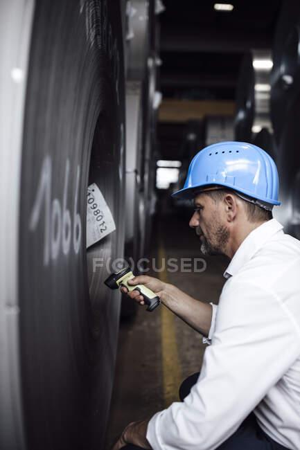 Empresario escaneando código de barras en rollos de acero mientras está parado en la industria - foto de stock