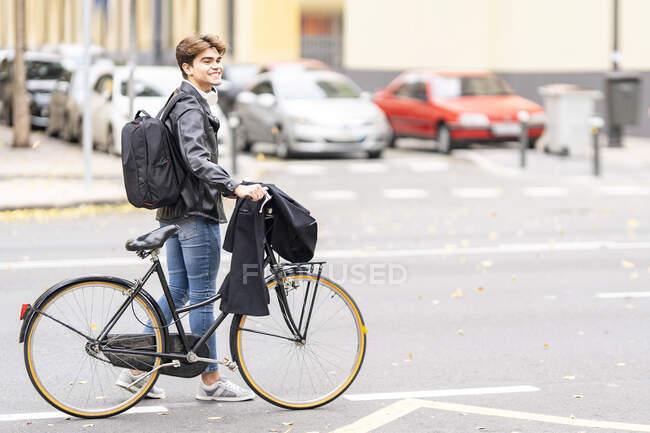 Посміхаючись, молодий чоловік ходить з велосипедом по вулицях. — стокове фото