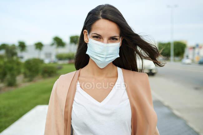 Молода жінка у захисній масці стоїть на вулиці. — стокове фото