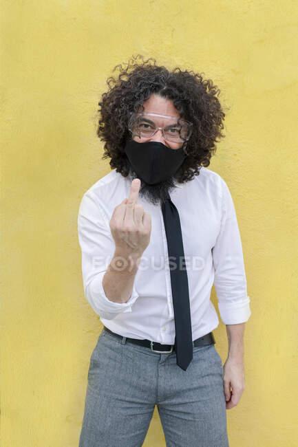 Uomo con maschera viso e occhiali che mostrano il segno della mano mentre in piedi contro il muro — Foto stock