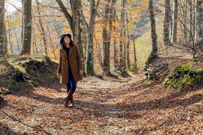 Mature woman wearing jacket standing with eyes closed on footpath in forest — Stock Photo