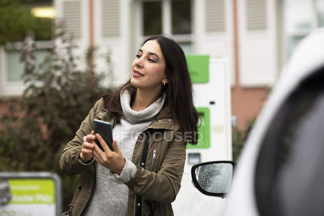 Beautiful woman holding smart phone by rental electric car at charging station — Stock Photo