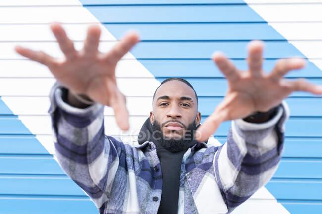 Молодий чоловік з холодним ставленням жестикулює проти синьо - білої стіни. — стокове фото