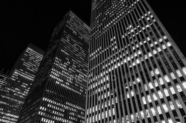Edificios modernos iluminados en el centro de Nueva York, Nueva York, EE.UU. - foto de stock
