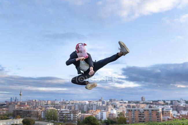 Maschera maschile professionale che indossa maiale praticare kickboxing mentre salta contro il cielo — Foto stock
