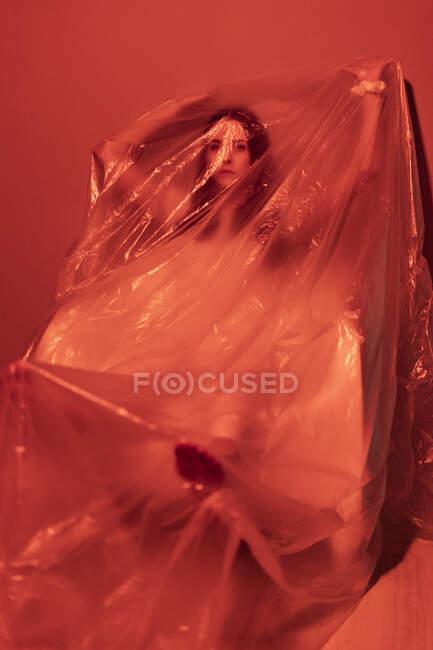 Mujer joven y preocupada con los brazos levantados cubiertos de plástico durante el brote de COVID-19 - foto de stock