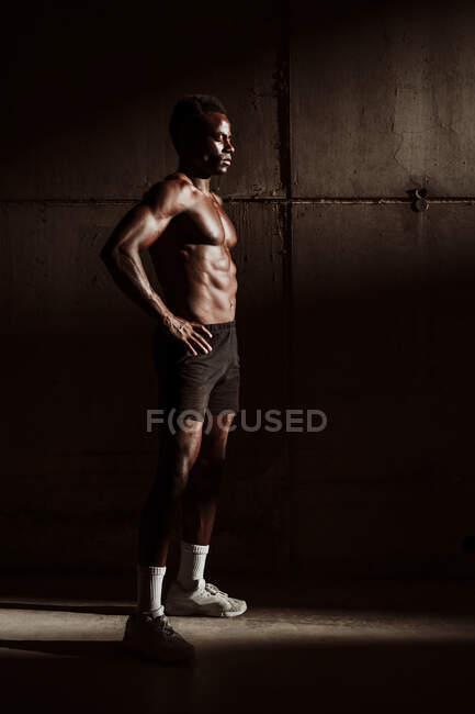 Deportista con la mano en el pecho desnudo en la cadera de pie por la pared gris durante el atardecer - foto de stock