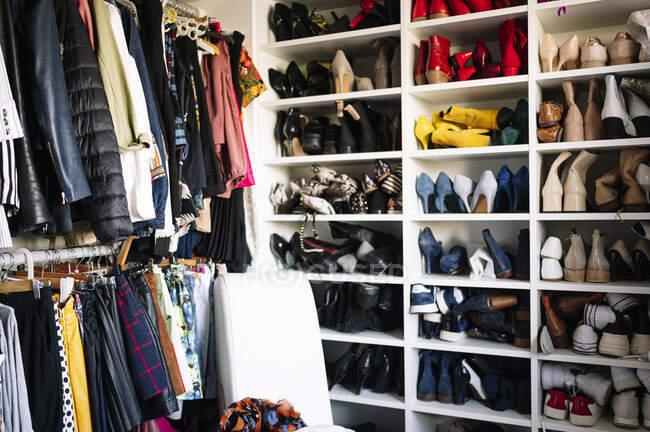 Abundância de calçado e roupas em guarda-roupa em casa — Fotografia de Stock