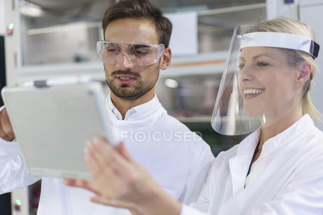Techniciens masculins et féminins discutant sur tablette numérique au laboratoire éclairé — Photo de stock