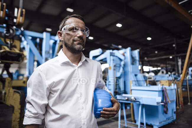Businessman wearing protective eyewear while holding helmet standing at industry — Stock Photo