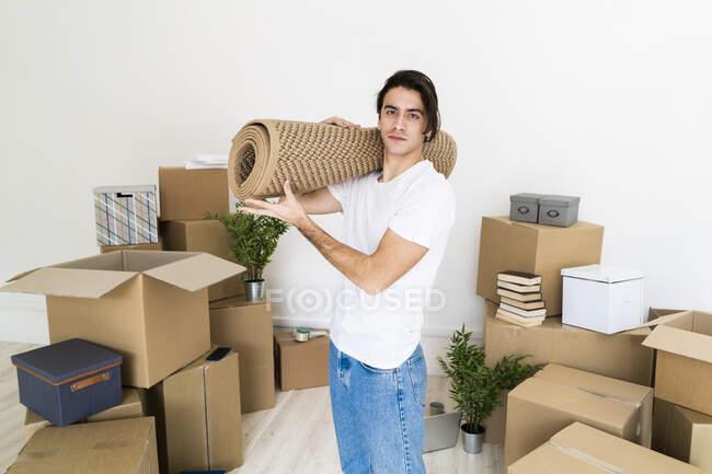 Jeune homme portant un tapis sur l'épaule tout en déménageant dans une nouvelle maison — Photo de stock
