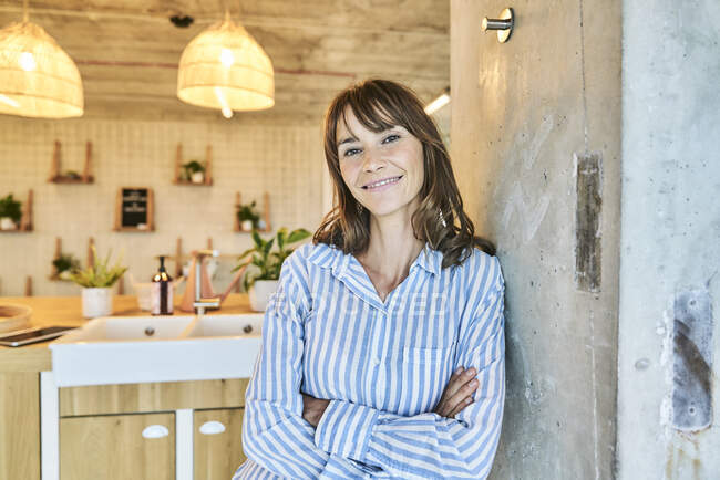 Smiling woman with arms crossed leaning on wall at home — Stock Photo