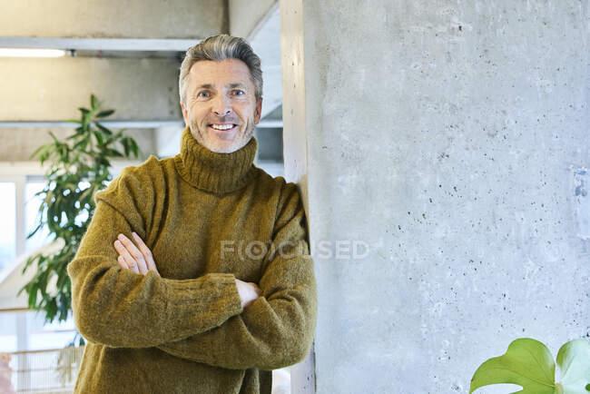 Hombre maduro con los brazos cruzados sonriendo mientras se apoya en el pilar en la oficina - foto de stock