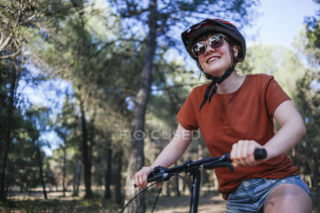 Happy young woman riding bicycle against trees at countryside — Stock Photo