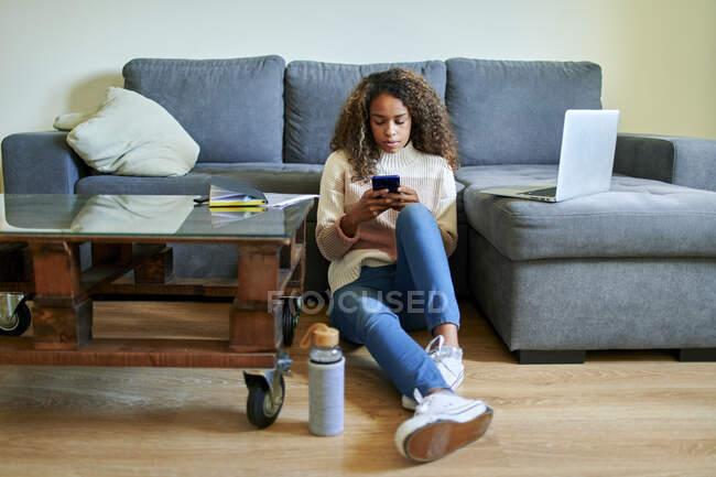 Молода жінка користується мобільним телефоном, сидячи на підлозі у вітальні. — стокове фото