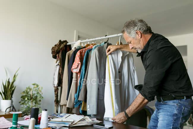 Camisa de medida de sastre macho madura con cinta métrica en el estudio de trabajo - foto de stock