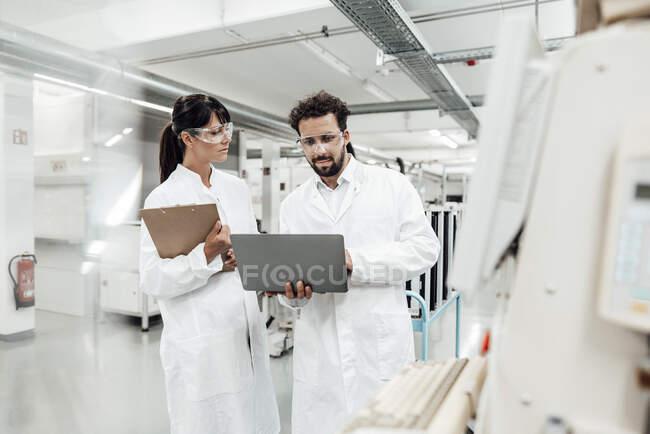 Femme scientifique regardant un collègue masculin en utilisant un ordinateur portable en laboratoire — Photo de stock