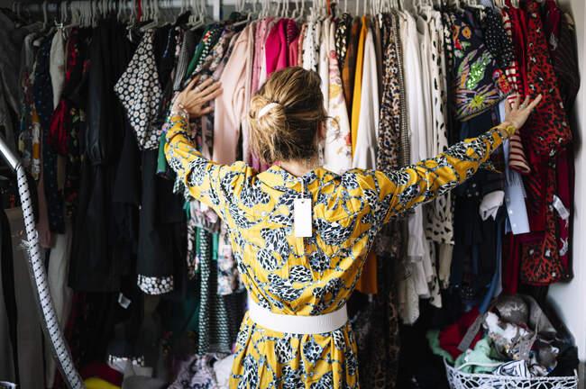 Mulher loira na moda em novo vestido amarelo escolhendo a partir de rack de roupas no apartamento — Fotografia de Stock