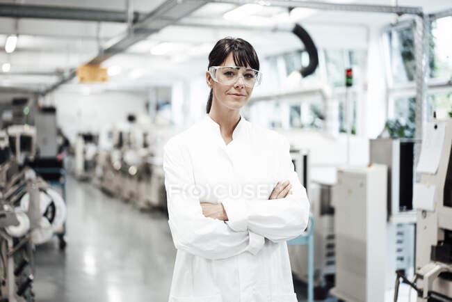 Scientifique confiante debout avec les bras croisés dans un laboratoire lumineux — Photo de stock