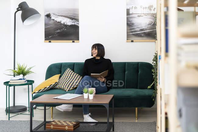 Щаслива молода жінка з книжкою, що відвернулася, сидячи у вітальні. — стокове фото
