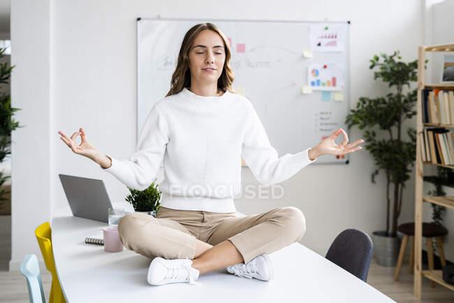 Молодая предпринимательница, занимающаяся йогой, сидя за столом в офисе — стоковое фото
