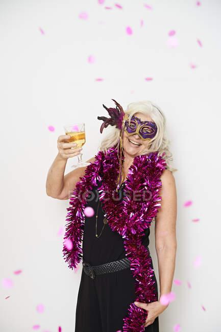 Улыбающаяся пожилая женщина, наслаждающаяся напитком, стоя на белом фоне — стоковое фото