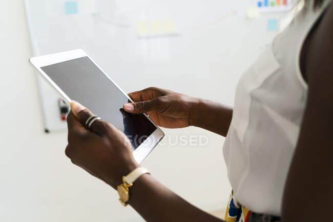 Empresaria sosteniendo tableta digital mientras está de pie en la oficina - foto de stock