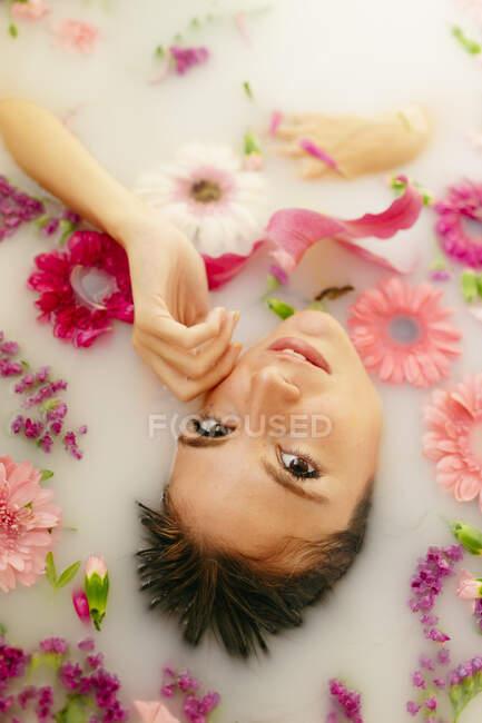 Beautiful woman taking milkbath in bathroom - foto de stock