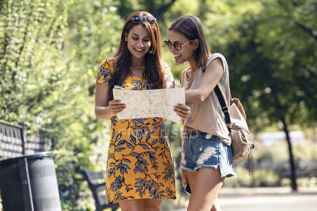 Посмішка жінок, які аналізують мапу, стоячи на площі Саграда Фамілія в Барселоні, Каталонія, Іспанія. — стокове фото