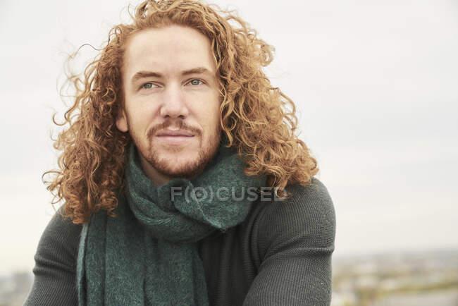 Созерцая длинные волосы, мужчина смотрит в сторону неба — стоковое фото