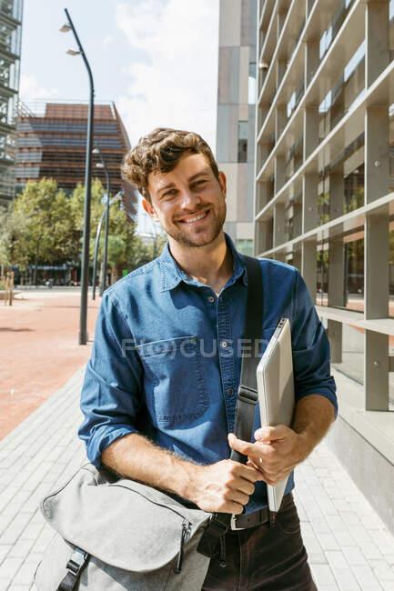 Sorridente giovane uomo d'affari in piedi sul sentiero in città durante la giornata di sole — Foto stock