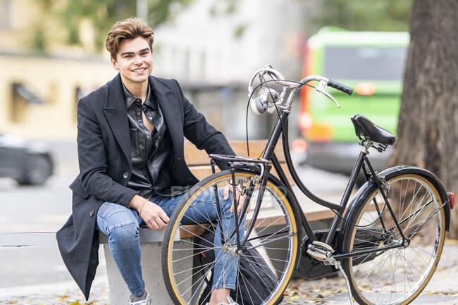 Bonito jovem sentado no banco de bicicleta na cidade — Fotografia de Stock