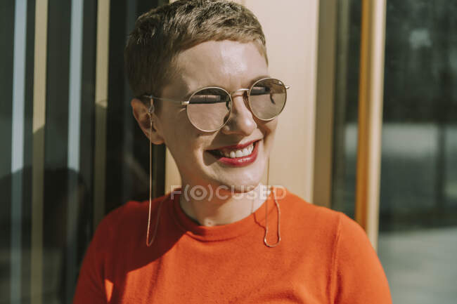 Mid adult woman wearing sunglasses while standing on sunny day — Stock Photo