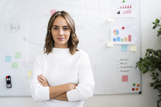 Confident businesswoman standing against whiteboard at office — Stock Photo