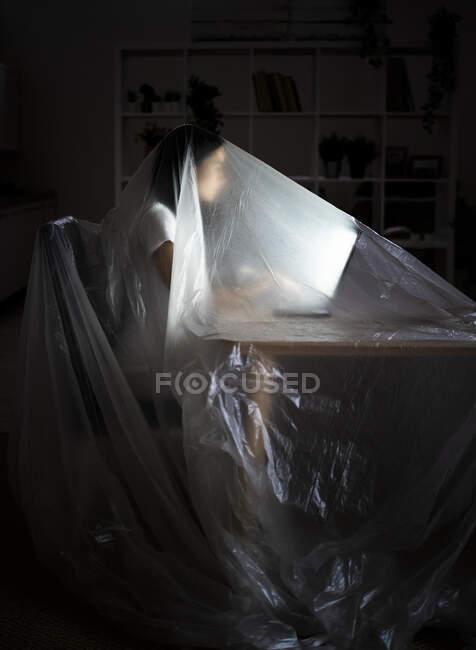 Mujer joven usando portátil en la mesa mientras está cubierta de plástico durante COVID-19 - foto de stock